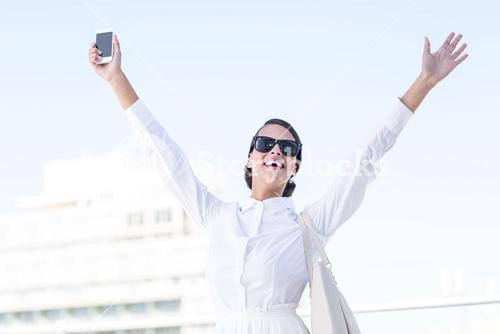 Euphoric woman holding smartphone with hands up