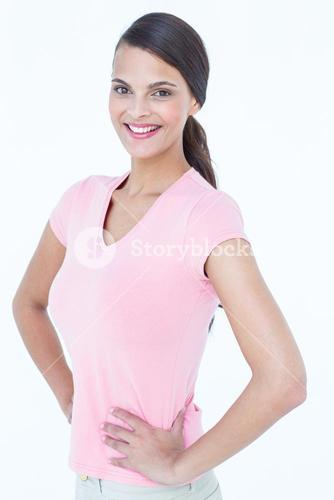 Happy brunette woman looking at camera with hands on hips