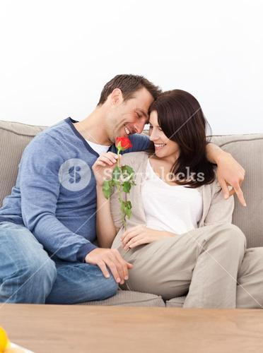 Enamored couple sitting together on the sofa