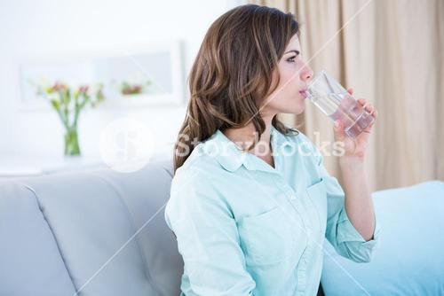 Thoughtful woman drinking a glass of water