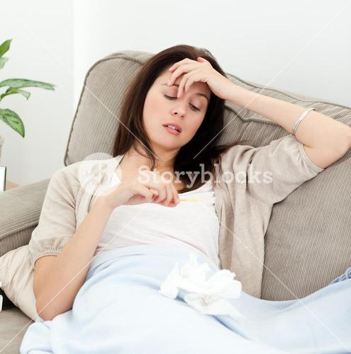 Sick woman looking at a thermometer while resting on the sofa