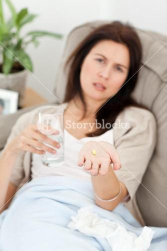 Sick woman taking her medicine on the sofa