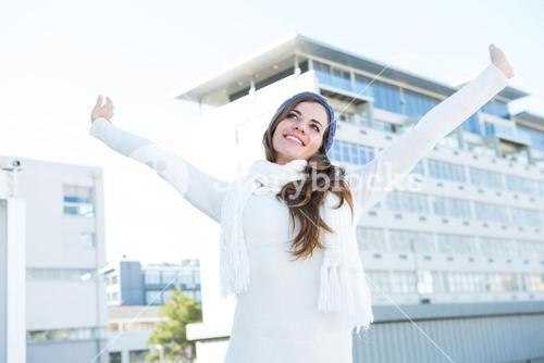 Pretty brunette with warm clothes raising hands