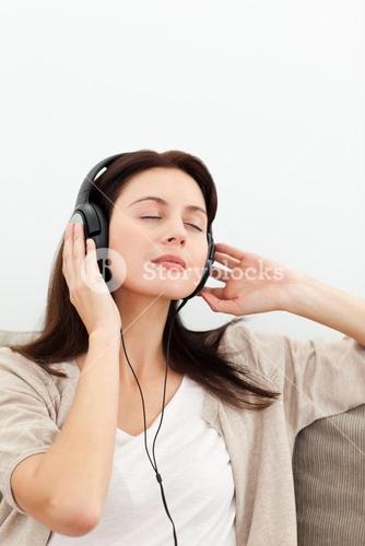 Serene woman listening to music on the sofa