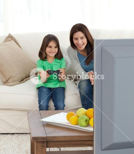 Pretty mom encouraging her daughter playing video games