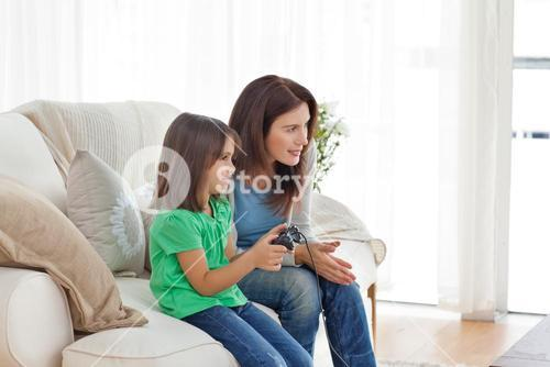 Attentive mother encouraging her daughter playing video games