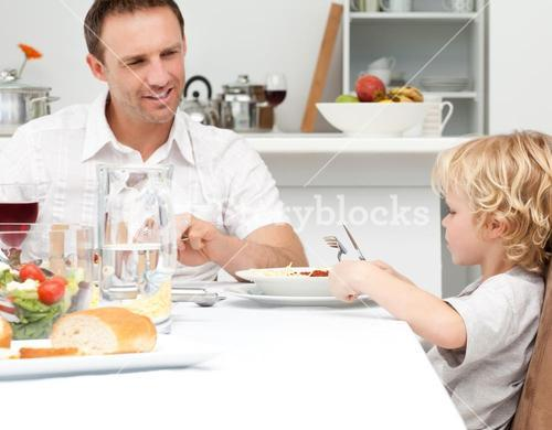 Happy dad looking at his son eating pasta