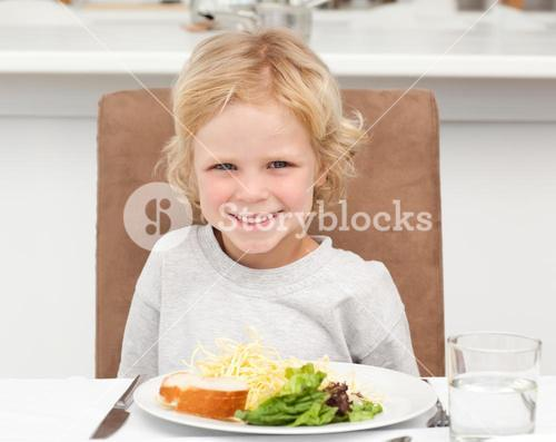 Cute little boy eating pasta and salad