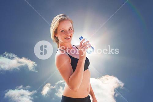 Composite image of fit blonde drinking water
