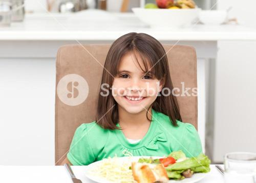 Portrait of a little girl eating pasta and salad