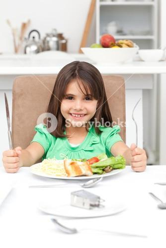 Adorable llittle girl holding forks to eat pasta and salad