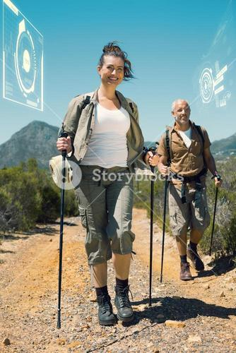 Composite image of happy hiking couple walking on mountain trail