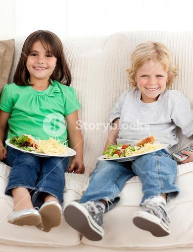 Happy brother and sister watching television while eating pasta