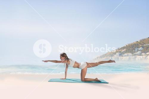 Composite image of gorgeous fit blonde in pilates pose on the beach