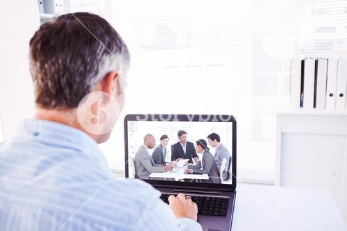 Composite image of man with grey hair using his laptop