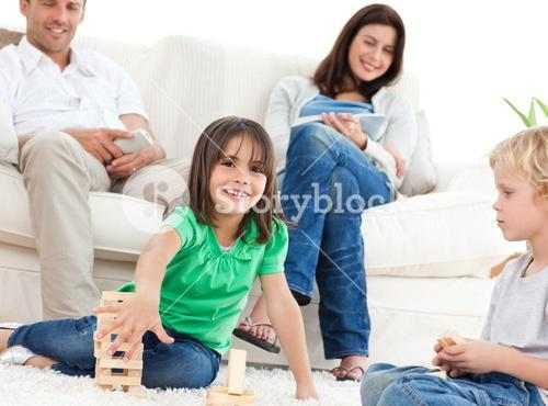 Happy children playing with dominoes in the living room