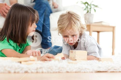 Cute little boy playing dominoes with his sister on the floor
