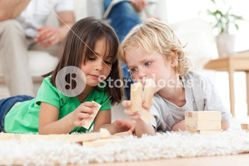 Little boy and girl playing with dominoes together