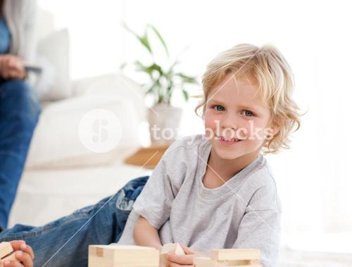 Cute child playing with dominoes in the living room