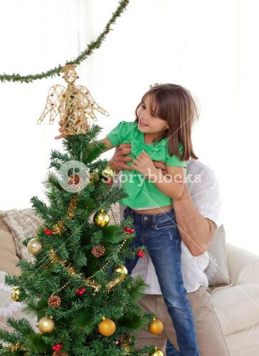 Attentive father holding her daughter to decorate the christmas tree