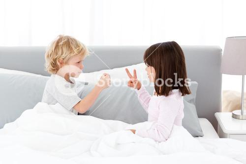 Cute brother and sister playing rock paper and scissors on a bed