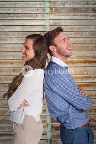 Composite image of happy young couple standing back to back