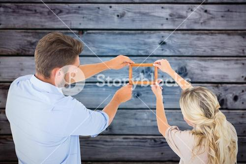 Composite image of attractive young couple hanging a frame