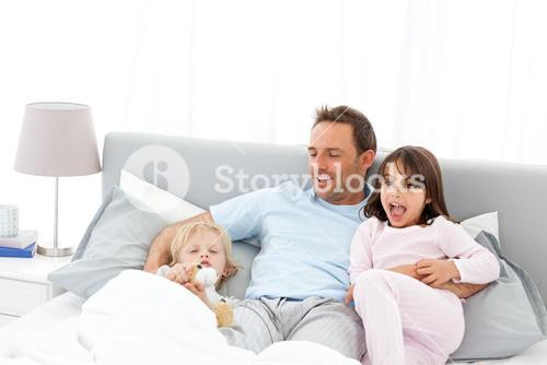 Handsome man playing with his children on a bed