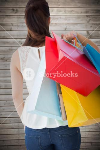 Composite image of rear view of brown hair holding shopping bags