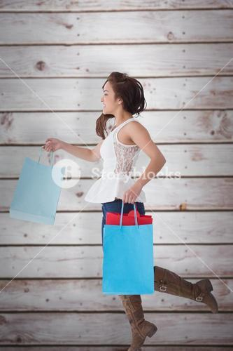 Composite image of happy brunette leaping with shopping bags
