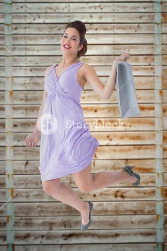 Composite image of happy brunette jumping with shopping bag