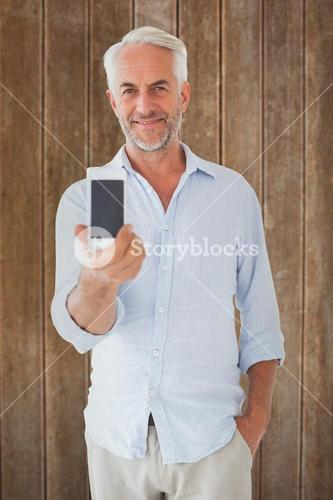 Composite image of smiling man showing smartphone to camera