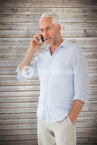 Composite image of serious man talking on the phone