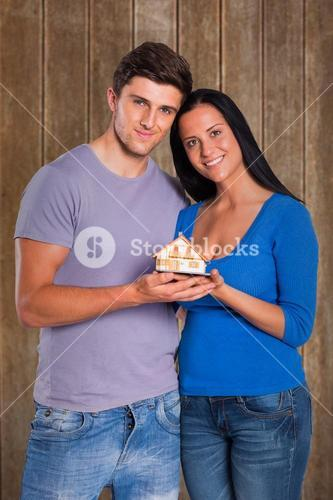 Composite image of young couple holding a model house