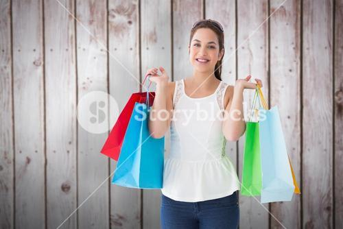 Composite image of cheerful brown hair holding shopping bags