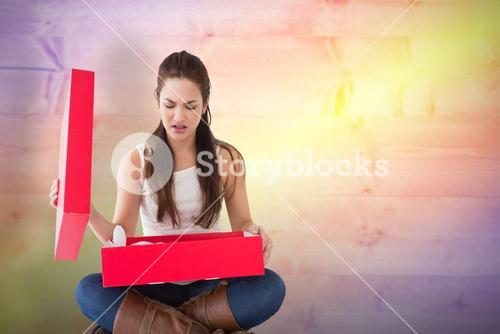 Composite image of unhappy brunette opening present