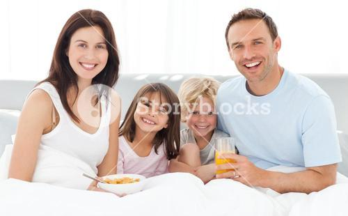 Cheerful family having breakfast together on the bed