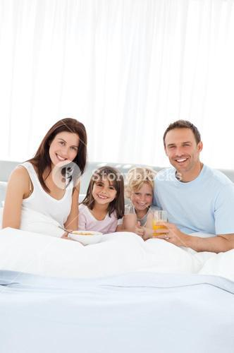 Happy brother and sister having breakfast with their parents on the bed