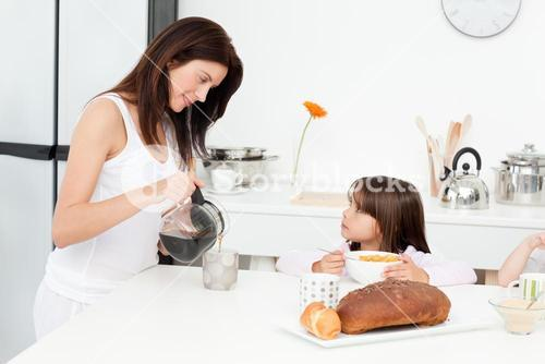 Pretty mom pouring coffee while her children are having breakfast