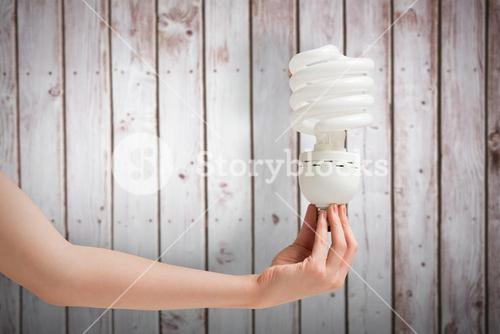 Composite image of hand holding energy efficient light bulb
