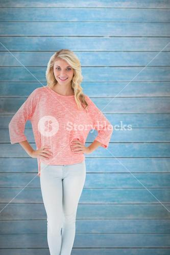 Composite image of pretty blonde smiling with hands on hips