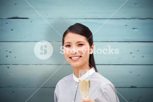 Composite image of businesswoman toasting with champagne