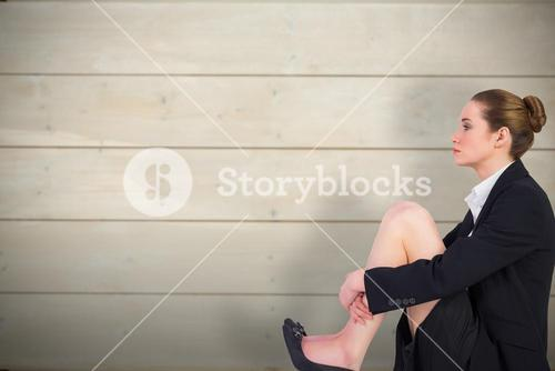 Composite image of businesswoman sitting on floor