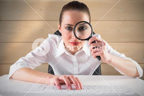 Composite image of businesswoman typing and looking through magnifying glass