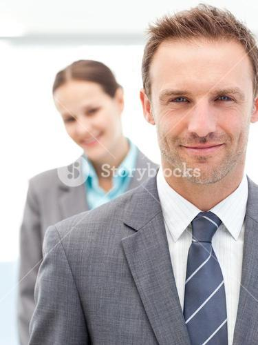 Confident businessman and businesswoman posing together in line