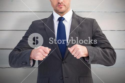 Composite image of mid section of a businessman with clenched fist