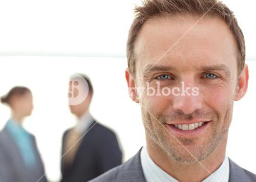 Cheerful businessman posing in front of his team while working