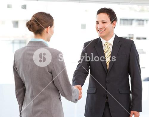 Cheerful businessman and businesswoman concluding a deal