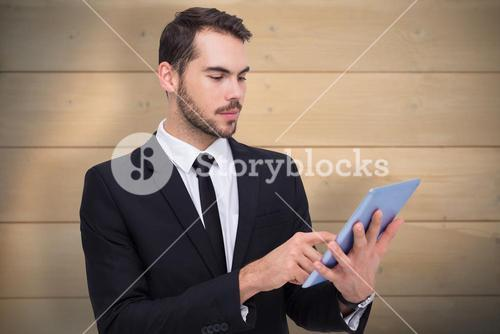 Composite image of cheerful businessman touching digital tablet