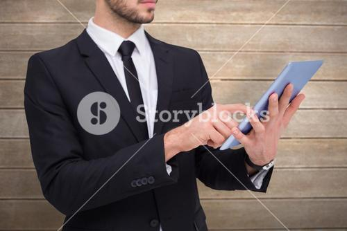 Composite image of mid section of a businessman using digital tablet pc